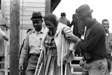 Two men helping a woman on crutches, probably after voting in a building in Lowndes County,...
