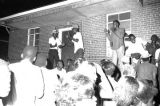 Men addressing an audience in front of an apartment building at Cleveland Court in Montgomery,...