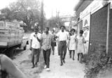 Group marching down a sidewalk in downtown Montgomery, Alabama, during a civil rights...