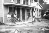 Men, women, and children on the porch in front of a small apartment building in Montgomery,...