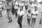 Richard Boone and others, marching through a neighborhood in Montgomery, Alabama, during a civil...