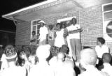 Idessa Williams addressing an audience in front of an apartment building at Cleveland Court in...