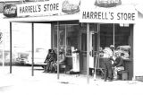 People seated on benches outside Harrell's Store in Hayneville, Alabama, during the trial of...