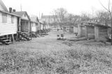 Outhouses behind a row of wooden houses in a neighborhood near Washington Park in Montgomery,...