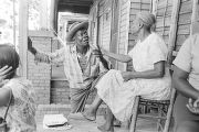 Elderly man and woman on the front porch of a wooden house in a neighborhood in Montgomery,...