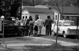 Protestors carrying signs, standing at the edge of a street in Prattville, Alabama, during a civil...