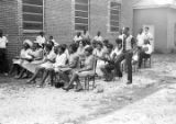 Audience seated in chairs outside a brick church building in Prattville, Alabama, during a meeting...