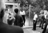 Stokely Carmichael walking down a sidewalk toward Rap Brown after Carmichael's release from prison...