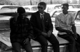 Stokely Carmichael and two other men, seated on the hood of a car parked outside Mt. Moriah...