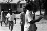 Group marching down an unpaved road in Prattville, Alabama, during a demonstration sponsored by...