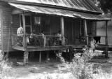 Men and women on the front porch of a wooden house, observing a march in Prattville, Alabama,...