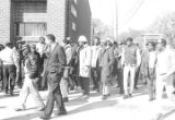 Wendell Paris and other students from Tuskegee Institute marching down a sidewalk beside the...