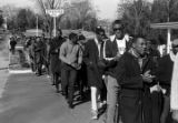 Students from Tuskegee Institute marching down a sidewalk on Old Montgomery Road during a...