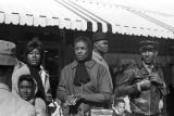 Women and men standing in front of a store in downtown Tuskegee, Alabama, during a student...