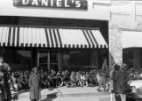 Students from Tuskegee Institute seated on the sidewalk outside Daniel's store, during a...