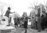 Willie Ricks standing on a car and addressing a crowd on the sidewalk in downtown Tuskegee,...
