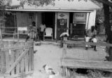 Two women and a man sitting in front of a wooden house in Newtown, a neighborhood in Montgomery,...