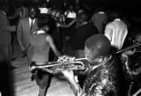 Members of The Sheiks playing the trumpet and trombone on the floor in front of the stage at the...