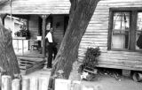 Man standing on the front porch steps of a wooden house in Newtown, a neighborhood in Montgomery,...