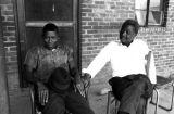Two men seated on the front porch of a brick house in Newtown, a neighborhood in Montgomery,...
