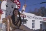 Young woman wearing an American Indian costume and riding on a float during the Peanut Festival...
