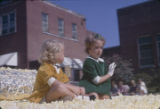 Two young girls riding on a float during the Peanut Festival parade in downtown Dothan, Alabama.