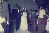 Susie Sanders and her father walking down the aisle of the church building during her wedding in...