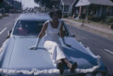 Young woman in a formal dress riding on the hood of a decorated car during the homecoming parade...