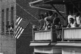 Onlookers watching Martin Luther King, Jr.'s funeral procession from a balcony.