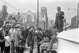 Man standing on a car and addressing the crowd outside Ebenezer Baptist Church at Martin Luther...