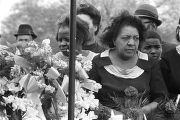 Close-up of mourners standing behind floral arrangements at Martin Luther King, Jr.'s grave site...