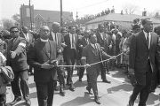 Three men holding a rope while walking down Auburn Avenue during Martin Luther King, Jr.'s funeral...