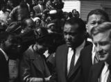 Man walking past the crowd on the side of the street during Martin Luther King, Jr.'s funeral...