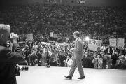Robert F. Kennedy walking across a stage before a large audience at the University of Alabama...
