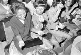 Young women singing and snapping their fingers in the audience during a performance of the Otis...