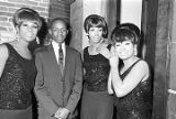 Young man standing with the Marvelettes, backstage at the Montgomery City Auditorium during a...