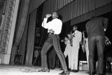 Otis Redding performing on stage during a concert at the Montgomery City Auditorium.
