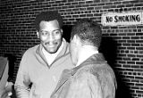 Otis Redding speaking to another man backstage at the Montgomery City Auditorium during a concert.