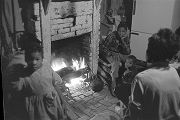 Marie, Katherine, Edwin, Charles, and Debra Bracy around the fireplace in the two-room shack where...