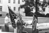 Klansman holding a Confederate flag, standing with other men around a car at a Ku Klux Klan rally...