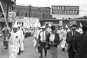 Klansmen carrying signs and a Confederate flag while marching in a parade during a Ku Klux Klan...