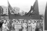Two Klansmen holding a burning banner at a Ku Klux Klan rally in Montgomery, Alabama.