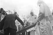 Man pouring lighter fluid on a banner during a Ku Klux Klan rally in Montgomery, Alabama.