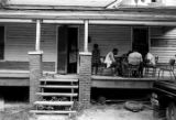 Four young men playing cards on the front porch of a wooden house in Newtown, a neighborhood in...