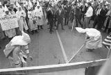 Klansmen setting down poles after burning a banner at a Ku Klux Klan rally in Montgomery, Alabama.