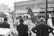 Klansmen carrying signs and flags in a parade during a Ku Klux Klan rally in Montgomery, Alabama.