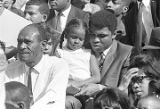 Muhammad Ali with a little girl, sitting in the bleachers during homecoming activities for Alabama...