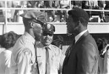 Muhammad Ali speaking with policemen on the football field during homecoming activities for...