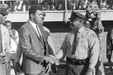 Muhammad Ali shaking hands with a policeman on the football field during homecoming activities for...