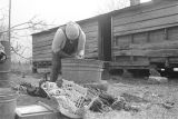 Wife of John Nixon washing clothes in a metal tub in her yard in Autaugaville, Alabama.